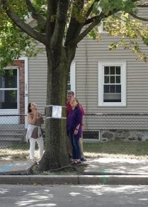 Pedestrians on Adams Street read one of the Tree Removal hearing notices. (Photo by Julia Malakie)